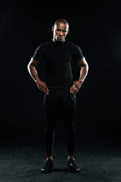 Serious afro american sports man, standing with arms on his hips Free Photo