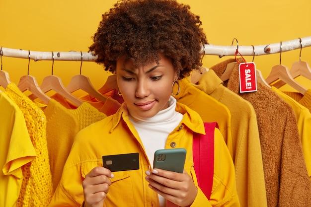 심각한 아프리카 여성은 백화점에서 온라인 쇼핑을 위해 휴대 전화로 신용 카드를 사용하고, 노란색 유행 셔츠를 입은 옷을 판매하고, 옷걸이에 다른 옷을 입습니다. 무료 사진