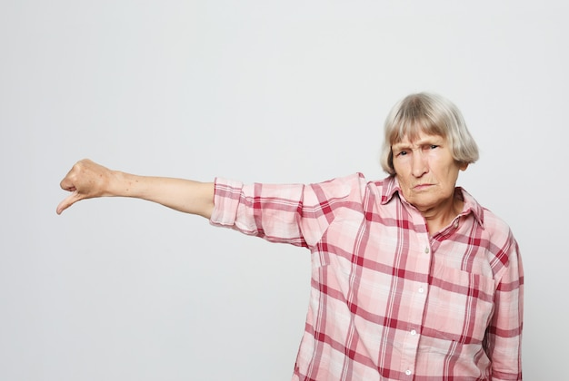 Serious aged woman pointing finger down. portrait of expressive grandmother with pink shirt. Premium Photo
