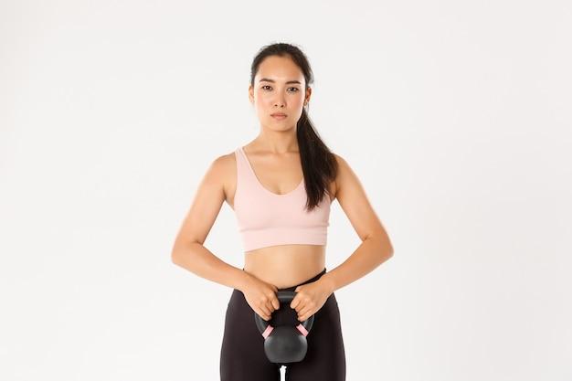 진지하고 집중된 아시아 강한 피트니스 소녀, 체육관에서 여성 운동 선수 운동, 흰색 배경에 서있는 Kettlebell 운동으로 스쿼트를하십시오. 프리미엄 사진