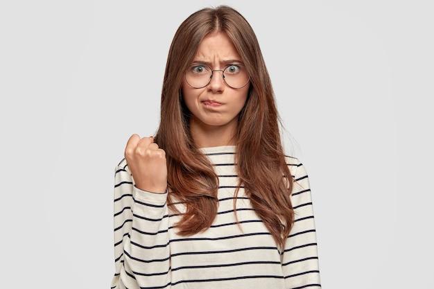 Серьезная злая сильная молодая женщина показывает сжатый кулак, выражает угрозу, одетая в полосатый свитер, демонстрирует женскую силу, недовольно смотрит, позирует у белой стены. концепция феминизма. Бесплатные Фотографии