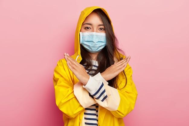 La ragazza asiatica seria fa il gesto di stop o di divieto, ha una malattia infettiva, tiene le braccia incrociate, indossa un impermeabile impermeabile Foto Gratuite