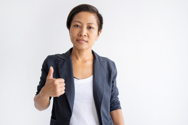Serious asian woman showing thumb up Free Photo