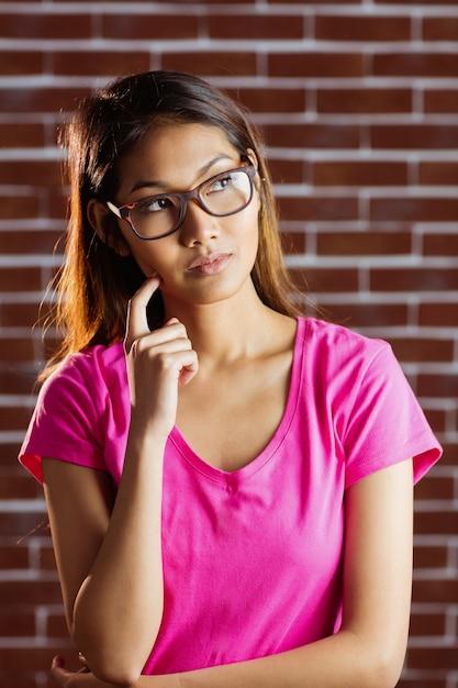 Серьезная азиатская женщина думая на кирпичной стене Premium Фотографии