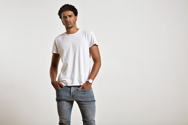 흰색 티셔츠를 입고 그의 꽉 청바지 주머니에 손으로 심각한 운동 젊은 아프리카 계 미국인 모델 무료 사진