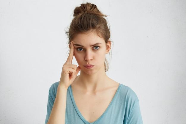 思慮深い表情の彼女のこめかみに指を当ててカジュアルな服を着ている髪結びの深刻な魅力的な青い目をした女性。 無料写真