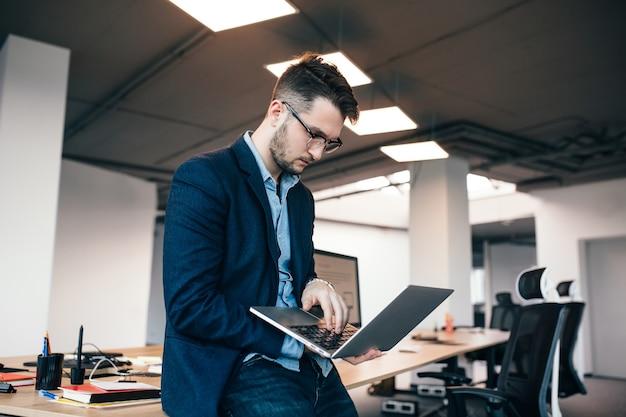 メガネの深刻な魅力的な男性がオフィスの職場の近くに立っています。彼は青いシャツ、暗いジャケットを着ています。彼はラップトップでタイプしています。 無料写真
