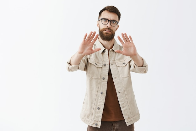 Serious bearded man in glasses posing against the white wall Free Photo
