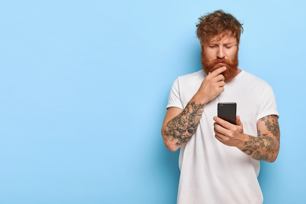 Серьезный бородатый мужчина внимательно смотрит в экран, читает новости в сети, обновляет программное обеспечение Бесплатные Фотографии