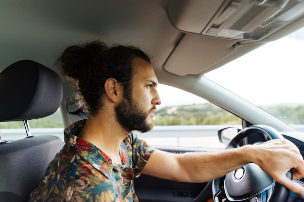 Serious bearded man riding in car Free Photo