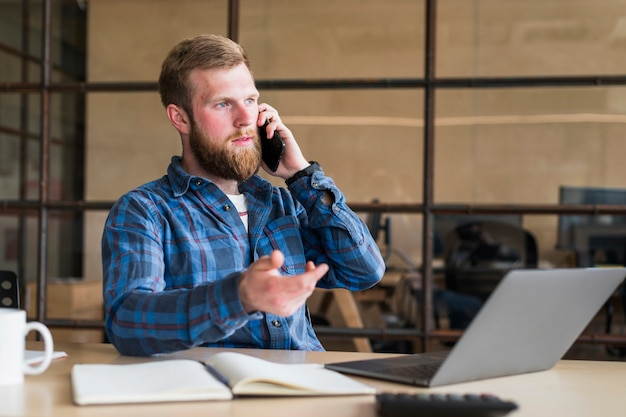 Serious bearded man talking on cellphone at workplace Free Photo