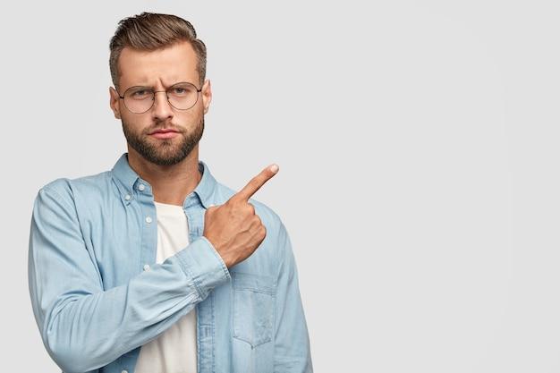 Uomo barbuto serio con un'espressione rigorosa, attira la tua attenzione su qualcosa, vestito con una camicia blu, mostra la direzione da qualche parte Foto Gratuite