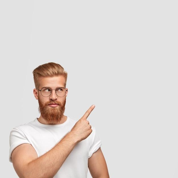Uomo barbuto serio con folta barba e baffi, guarda da parte, indossa gli occhiali Foto Gratuite