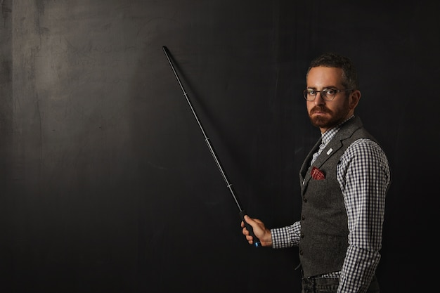 Serious bearded professor in plaid shirt and tweed vest, wearing glasses and looking condemn, shows something on school black board with his pointer Free Photo