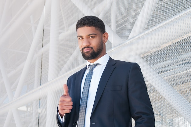 Serious black business man showing thumb up Free Photo