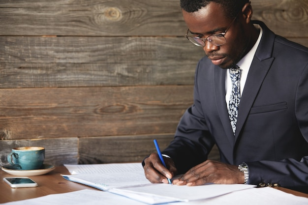 Серьезный черный корпоративный работник в строгом костюме и очках, подписывающий выгодный контракт Бесплатные Фотографии