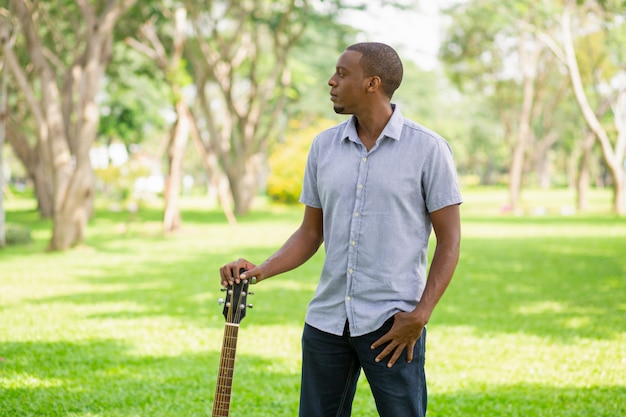Serious black man holding guitar by headstock in park Free Photo