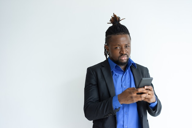 Serious black man holding and using smartphone Free Photo