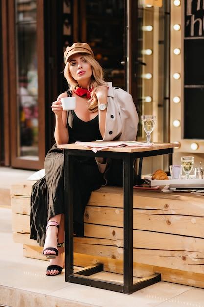 屋外カフェで身も凍るようにお茶を楽しんでいる黒い靴を履いた真面目なブロンドの女の子。魅力的な若い女性は、コーヒーを片手に、スタイリッシュなサンダルと茶色の帽子をかぶっています。 無料写真