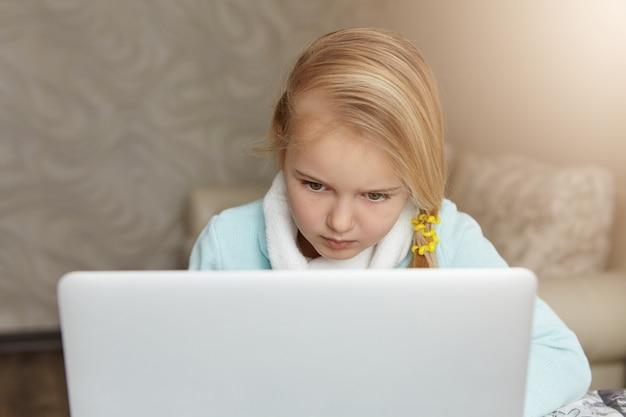 開いているラップトップの前に座っている深刻な金髪少女 無料写真