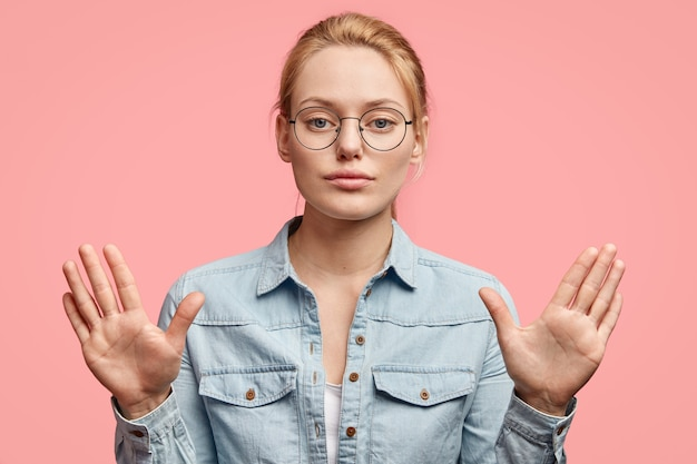 Serious blonde woman with confident expression, shows palms, makes stop gesture, doesn`t allow to do something, wears fashionable clothes, isolated on pink wall Free Photo