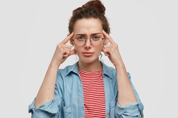 Bella giovane femmina seria dagli occhi blu con gli occhiali, tiene le dita sulle tempie, ha un'espressione intelligente e premurosa, cerca di ricordare qualcosa in mente, ha la pelle lentigginosa e un aspetto specifico Foto Gratuite