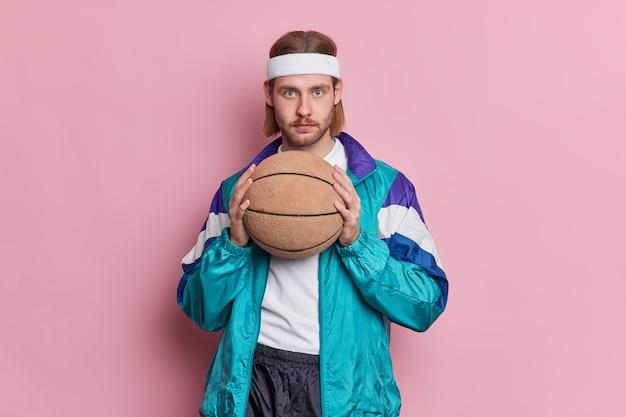 無精ひげの長い髪の真面目な青い目の男性バスケットボール選手は、白いヘッドバンドとスポーツ服を着てゲームをプレイする準備ができてボールを保持します。 無料写真
