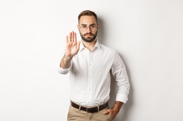 Серьезный босс в очках показывает знак остановки, говорит нет, что-то запрещает, стоит белым Бесплатные Фотографии