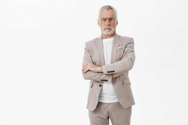 真面目な偉そうな老人実業家は腕を組んで自信を持って見える 無料写真