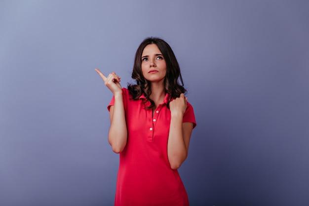 캐주얼 빨간 드레스를 찾는 심각한 갈색 머리 여자. 보라색 벽에 고립 잠겨있는 매력적인 여자의 초상화. 무료 사진