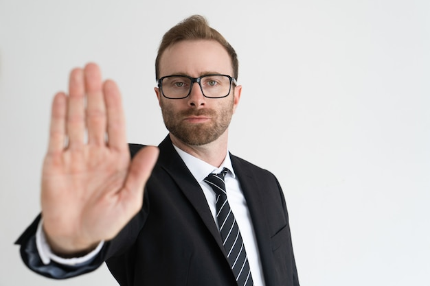 Serious business man showing open palm or stop gesture and looking at camera. Free Photo