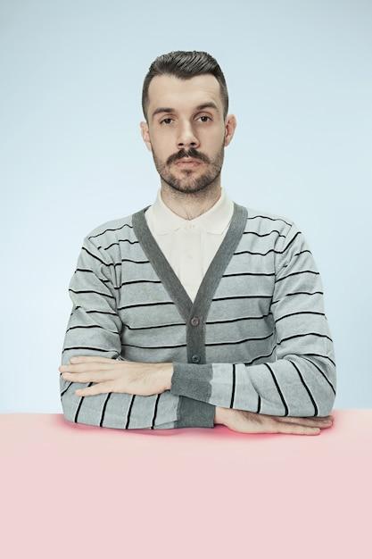Серьезный деловой человек, сидящий за столом на синем фоне студии. портрет в стиле минимализм Бесплатные Фотографии