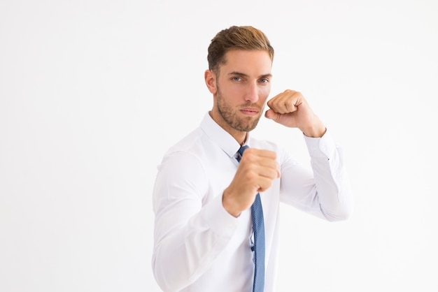 Serious business man standing in boxing pose Free Photo