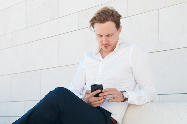 Serious business man using smartphone on bench outdoors Free Photo