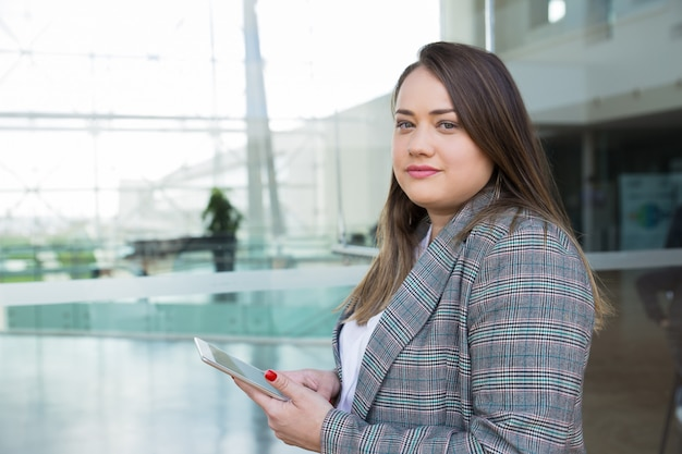 Serious business woman holding tablet outdoors Free Photo