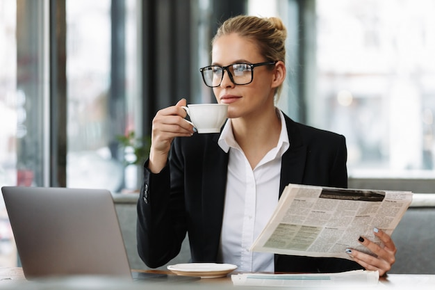 Serious business woman reading newspaper. Free Photo