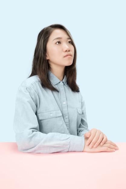 トレンディな青いスタジオの背景に孤立して見上げる、テーブルに座っている深刻なビジネス女性。女性の半身像。 無料写真