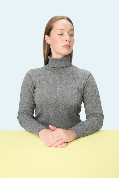 ピンクのスタジオの背景にテーブルに座っている深刻なビジネス女性。 無料写真