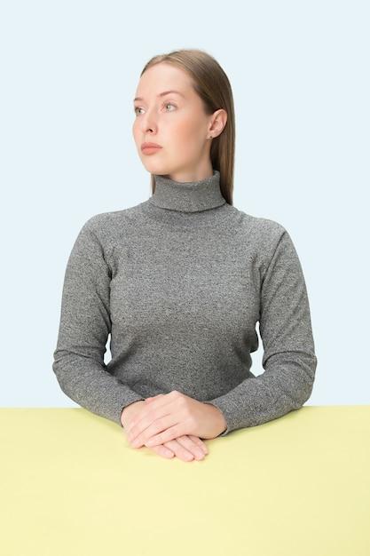 미니멀리즘 스타일의 초상화 테이블에 앉아 심각한 비즈니스 우먼 무료 사진