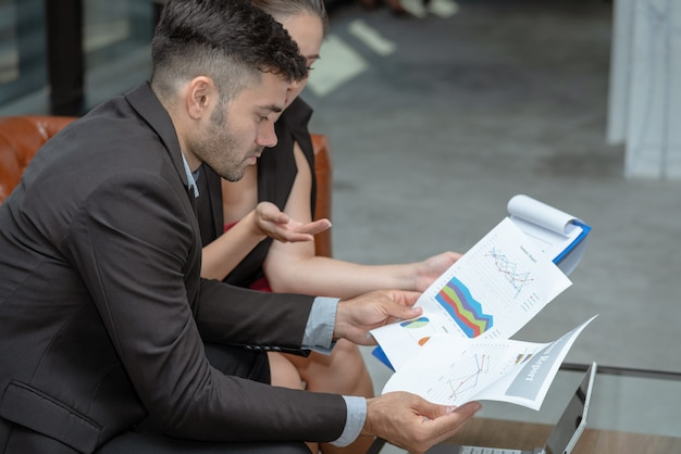Serious businessman and businesswoman meeting together looking business summary financial report in office Premium Photo