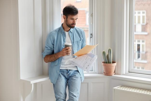 Imprenditore serio legge il testo del contratto, analizza la documentazione, concentrato sulle informazioni finanziarie Foto Gratuite