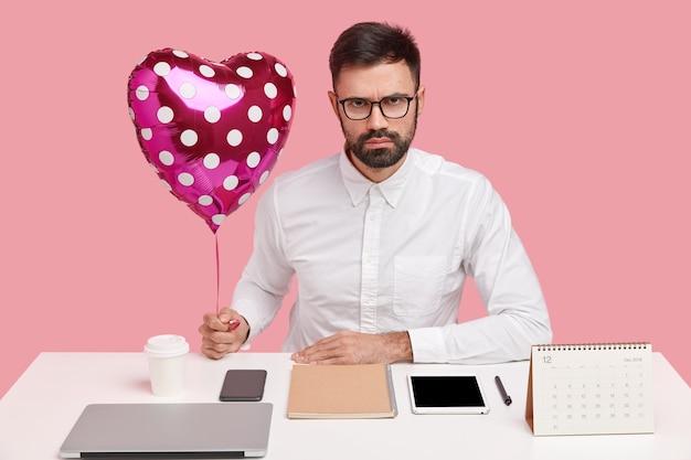 Серьезный бизнесмен получает валентинку от подруги на рабочем месте, держит воздушный шар в форме сердца, позирует за рабочим столом Бесплатные Фотографии
