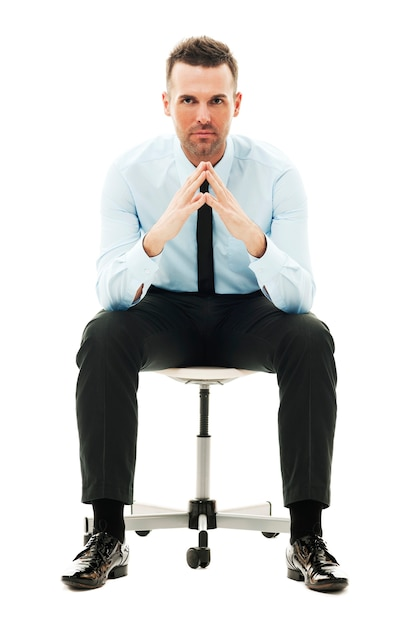 Serious businessman sitting on chair Free Photo