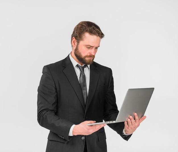 Serious businessman using laptop Free Photo