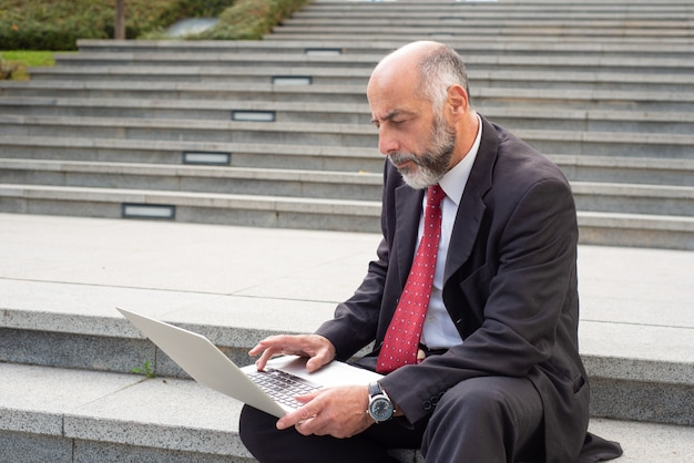 Serious businessman with laptop computer on street Free Photo
