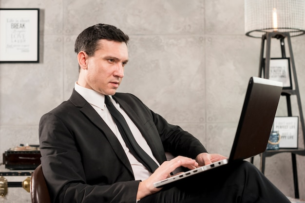 Serious businessman with laptop working at home Free Photo