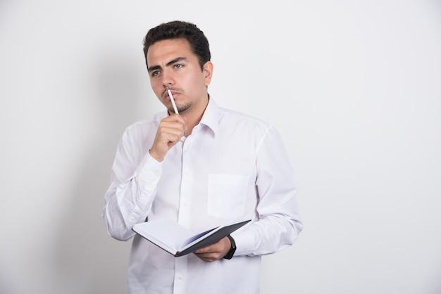 Uomo d'affari serio con il taccuino che pensa duro su priorità bassa bianca. Foto Gratuite