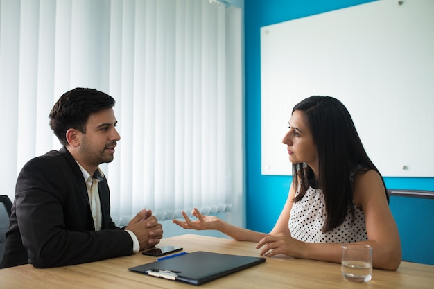 Serious businesswoman and businessman talking in boardroom Free Photo