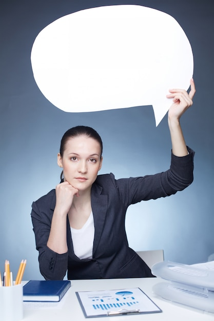 Serious businesswoman with a speech bubble Free Photo
