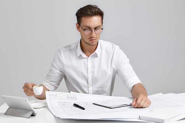 Designer maschio serio e impegnato vestito in modo formale, guarda attentamente i progetti, beve caffè o espresso. Foto Gratuite